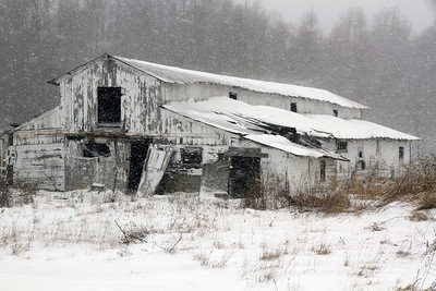 An old horse stable in disrepair during a snow winter storm.
