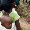 Criança com a irmã às costas, observa as mulheres na monda da horta comunitária de Darsalam - tabanca no sector de Pitche, região de Gabú.