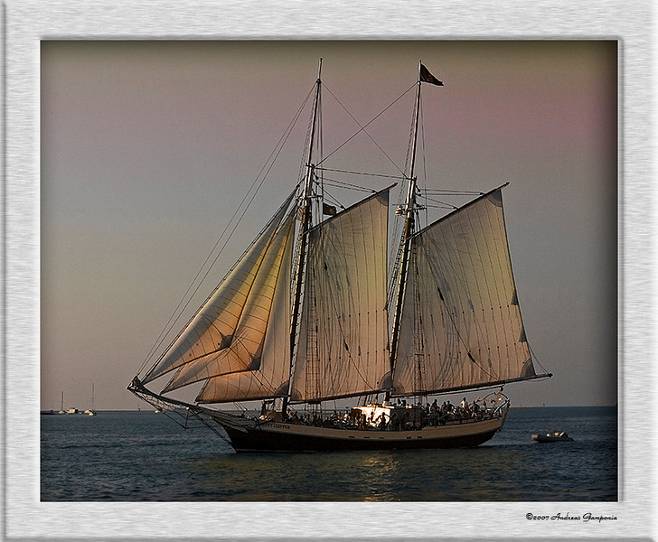 One of the sunset cruise schooners departing Schooner Wharf as seen from the sunset pier while sippin a rum runner....  The light of the lowering sun lights the sails with a warm glow.