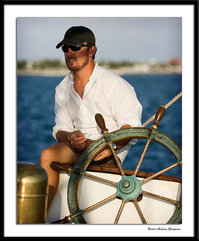 """The Captain of the vessel - """"Appledore"""" while under way on a sunset champagne sail escursion."""