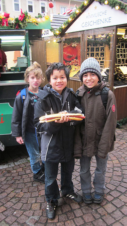 Germany, Heidelburg, Kids at Christmas Markets with Hot Dog nearly as big as them