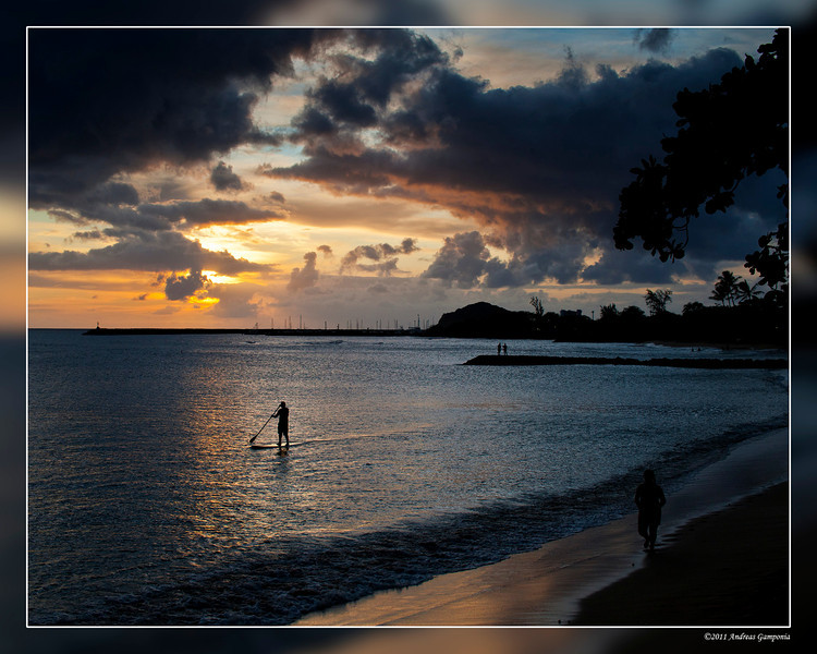 Sunset on the beach in front of our cabins in Waianae with a board paddler making his way across the bay.