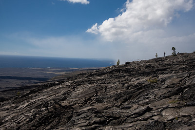 Lava flow leading to the sea with volcanic haze in the background