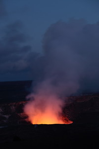 The lava in the innermost crater of Kilauea Volcano illuminating its own smoke after sunset.