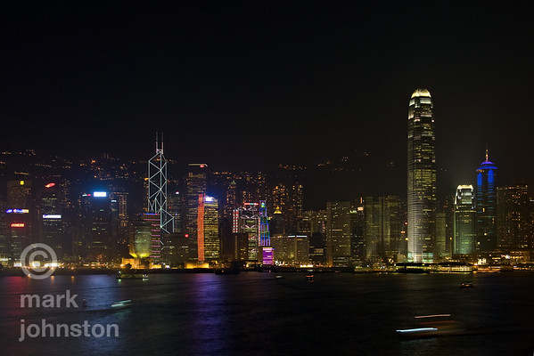 Hong Kong skyline looking south across Victoria Harbor from the Kowloon side.  Every evening at 8 PM, many of the tallest buildings are illuminated by special lighting including flashes of color and lasers.