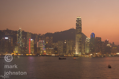 Hong Kong skyline at sunset, looking south across Victoria Harbor from the Kowloon side.