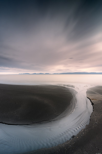 Flat stream through black sand