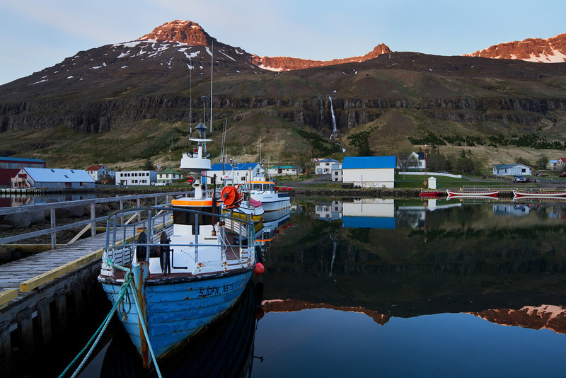 <H3> -Seydisfjordur- </H3> A lovely fishing town in the East Fjords region of Iceland. This night was calm and peaceful as can be seen by the mirror reflection - there is a decent sized waterfall tumbling over the cliff in the back - no big deal..see 'em all the time ;)