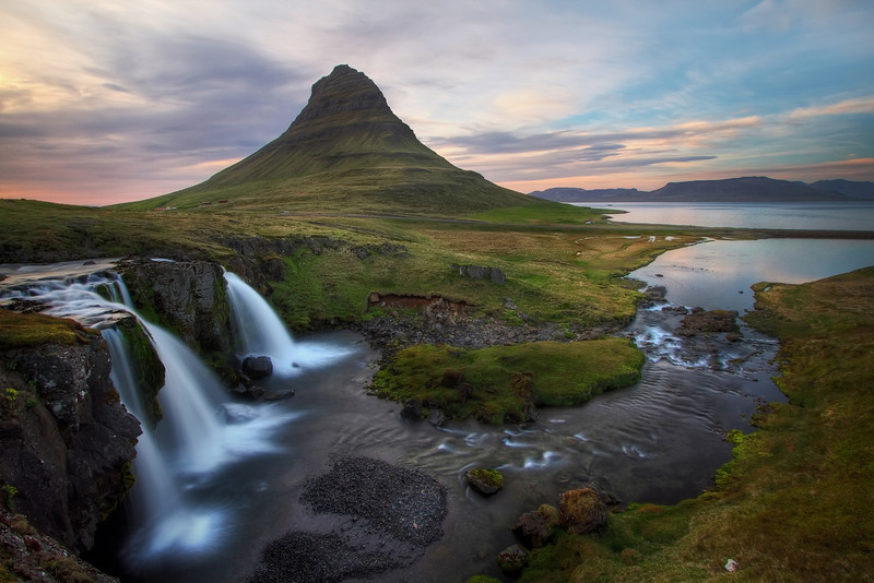 <H3> Kirkjufell </H3> This is probably the posterchild mountain of Iceland with its unique shape formed over time by erosion. The three-curtain watefall in the foreground doesnt hurt the view either :)