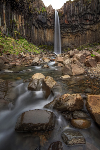 <H3>Svartifoss </H3> A short hike in Skaftafell National Park takes you to this gem of a waterfall. Svartifoss tumbles down a wall of basalt columns that gives it a very unique look. This shot is taken a bit down river but it is possible to go all the way and touch the columns.
