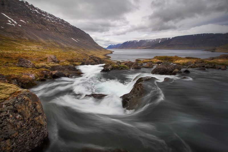 <H3> Flow </H3> Here is a view from near the top of Dynjandi Falls looking back out to the fjord - there is a certain quiet experienced in this remote area in Iceland despite the thundering flow of the several cascades of waterfall behind me.