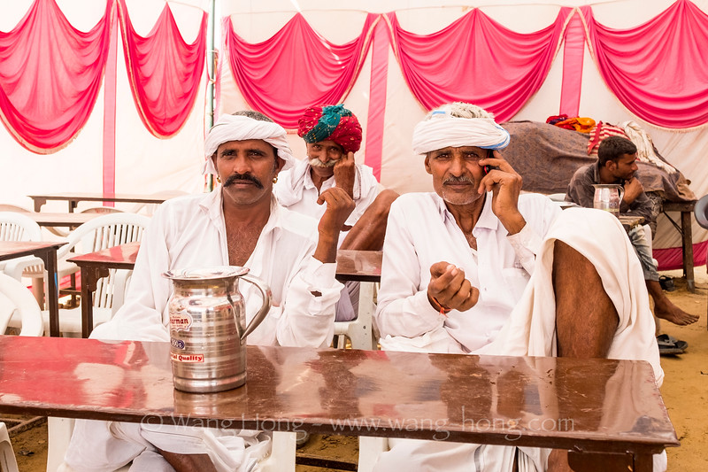 Men resting in a food tent at the Camel Fair, 2019.