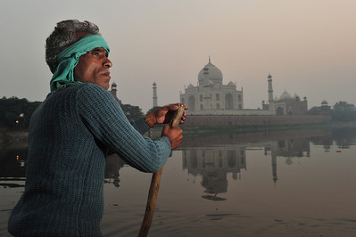 Boatman on river behind Taj Mahal