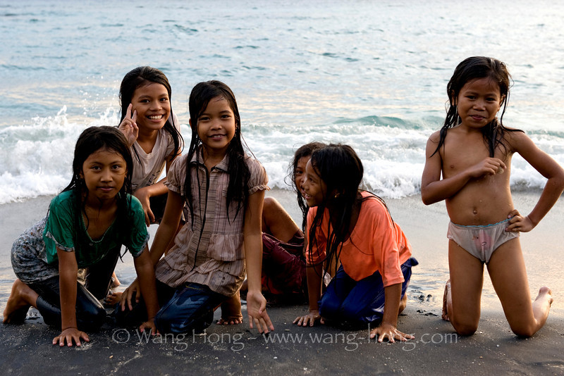 Lively girls enjoying water at Sunset in Mangsit Village on Lombok