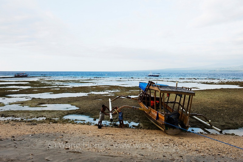 Cleaning the glass-bottom boat at the end of day, Gili Air