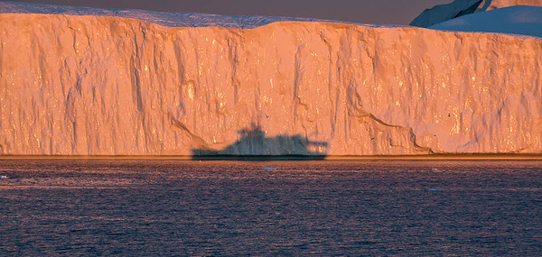 Boat shadow at sunset on Iceberg, Disko Bay, Illulissat, Greenland