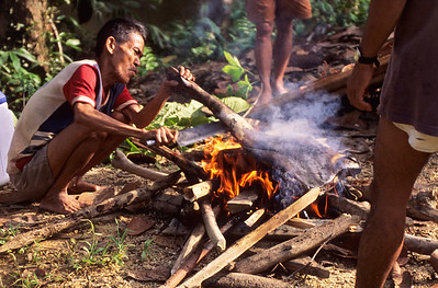 Iban man cooking a wild pig, which he killed in the jungle.  Batang Ri river, Sarawak, Malaysia.