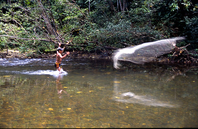 Catching fish with a weighted throw net.  Were as I would starve to death, these people could pluck food out of the jungle as though it was an open air market.  Batang Ri river, Sarawak, Malaysia.  1996