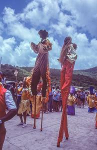Stilt walkers in Parade.   Cruz Bay, St. John Island, US Vergin islands.  1979