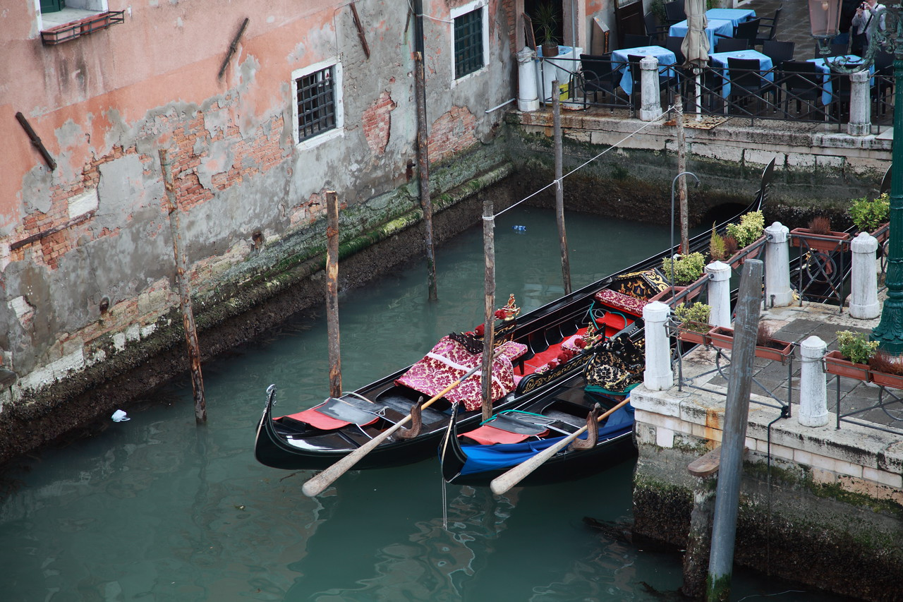 Gondolas are moored side-by-side in a small canal in Venice, Italy.
