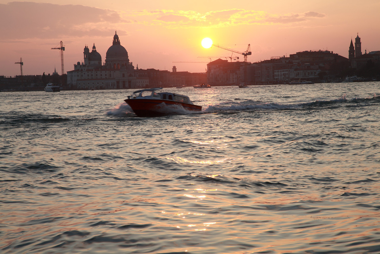 The sun sets over Venice, and the Santa Maria Della Salute is a silhouette against the sky