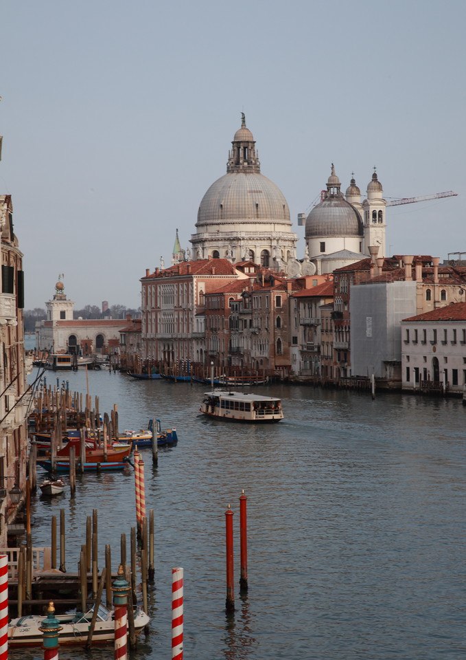 Canal Grande, Venice. The dome of the basilica of Santa Maria della Salute towers above the buildings. Red gondola mooring poles are in the foreground.