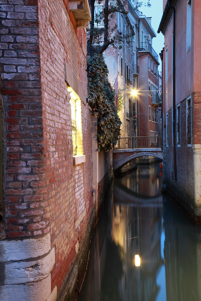 A bridge is reflected in the water of a narrow canal in Venice