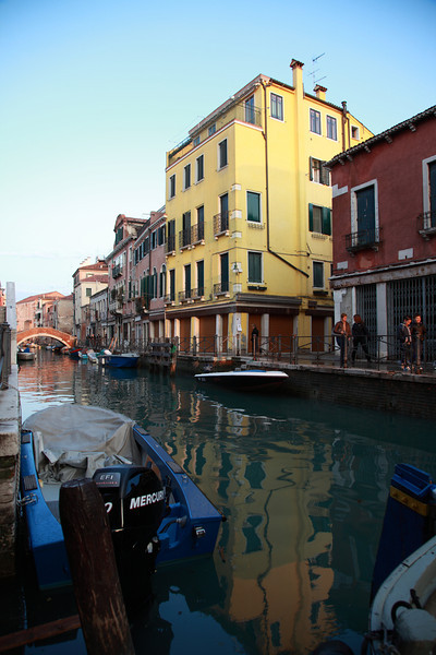 Yellow building reflected in the canal water in Venice, Italy