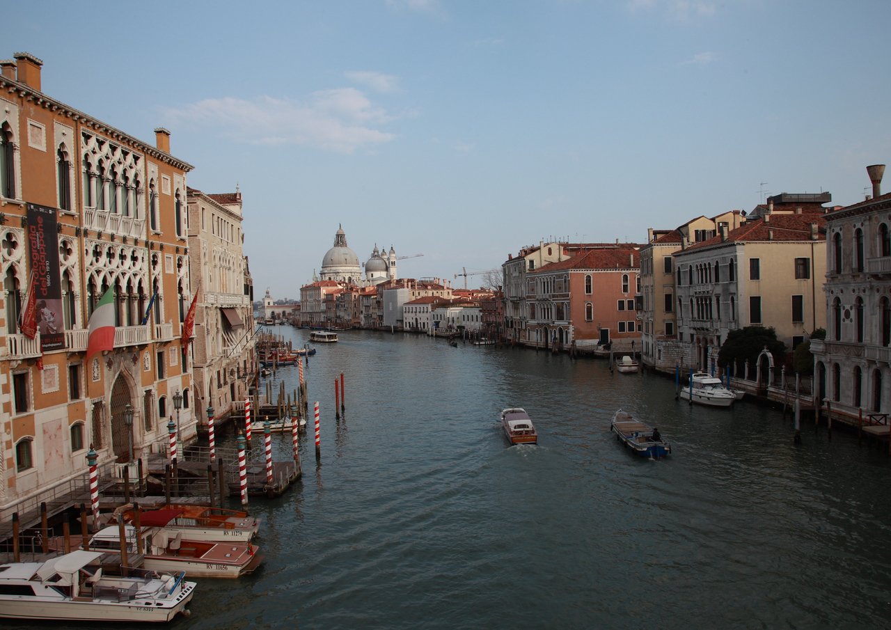 Canal Grande, Venice. The dome of the basilica of Santa Maria della Saluteis in the background. Candy-cane striped gondola mooring poles are seen on the left.