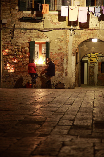 A couple sitting outside a bar on a square in Venice, Italy, at night
