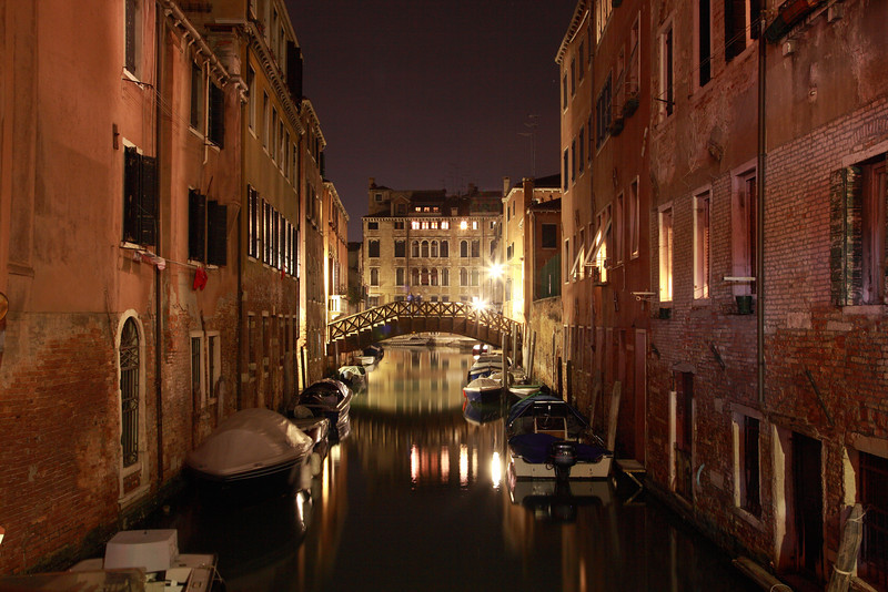 A bridge and gondolas are reflected in the water of a narrow canal in Venice