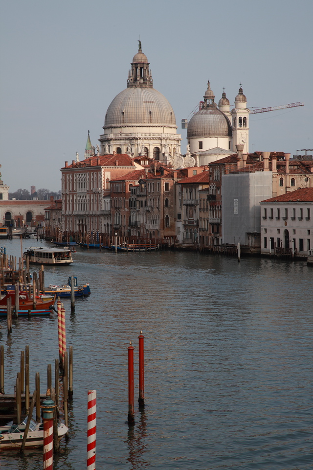 Canal Grande, Venice. The dome of the basilica of Santa Maria della Saluteis in the background. Red gondola mooring poles are in the foreground.