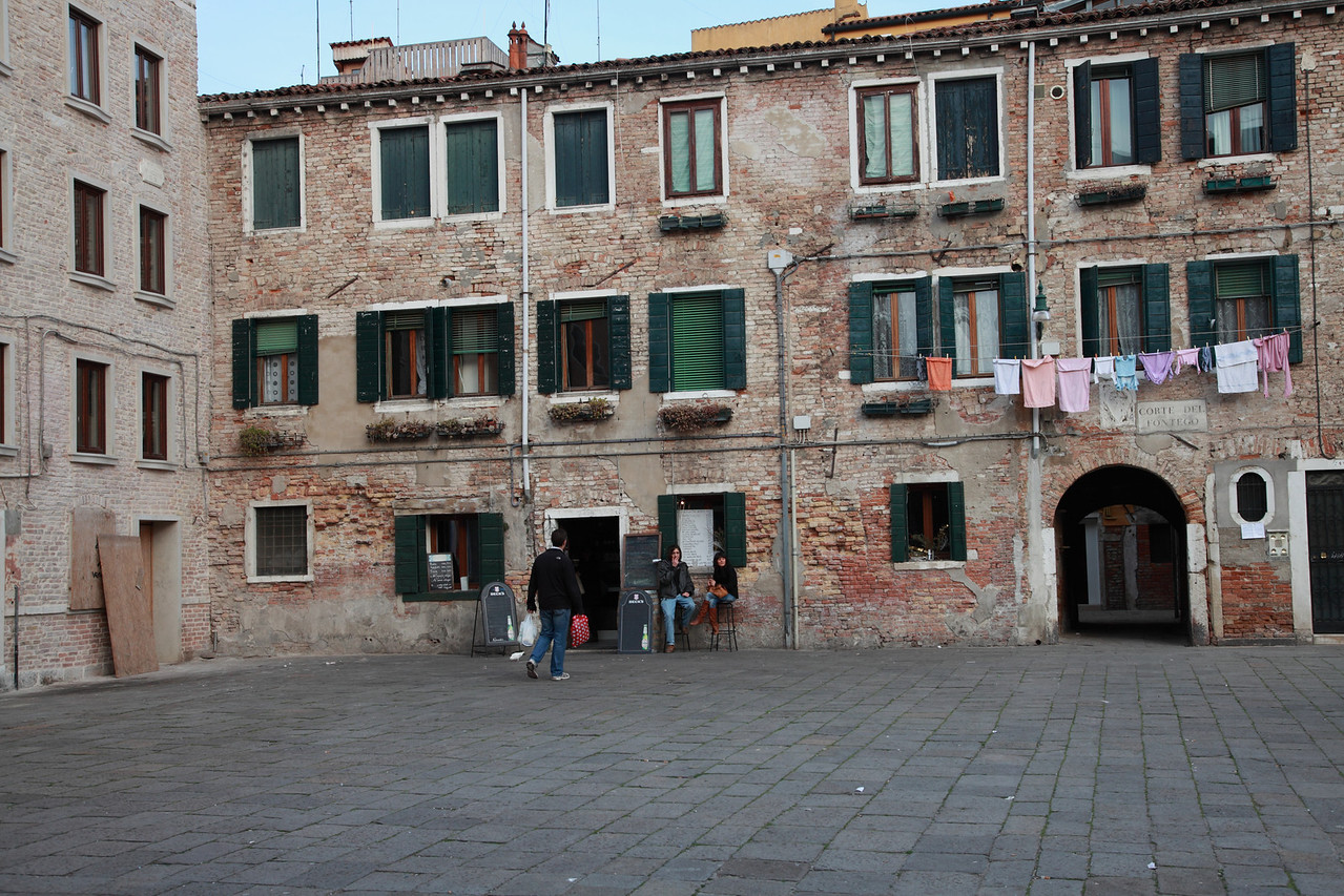 Laundry hanging out to dry outside the windows above a square in Venice, Italy