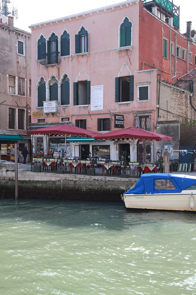 Restaurant tables along a canal in Venice, Italy
