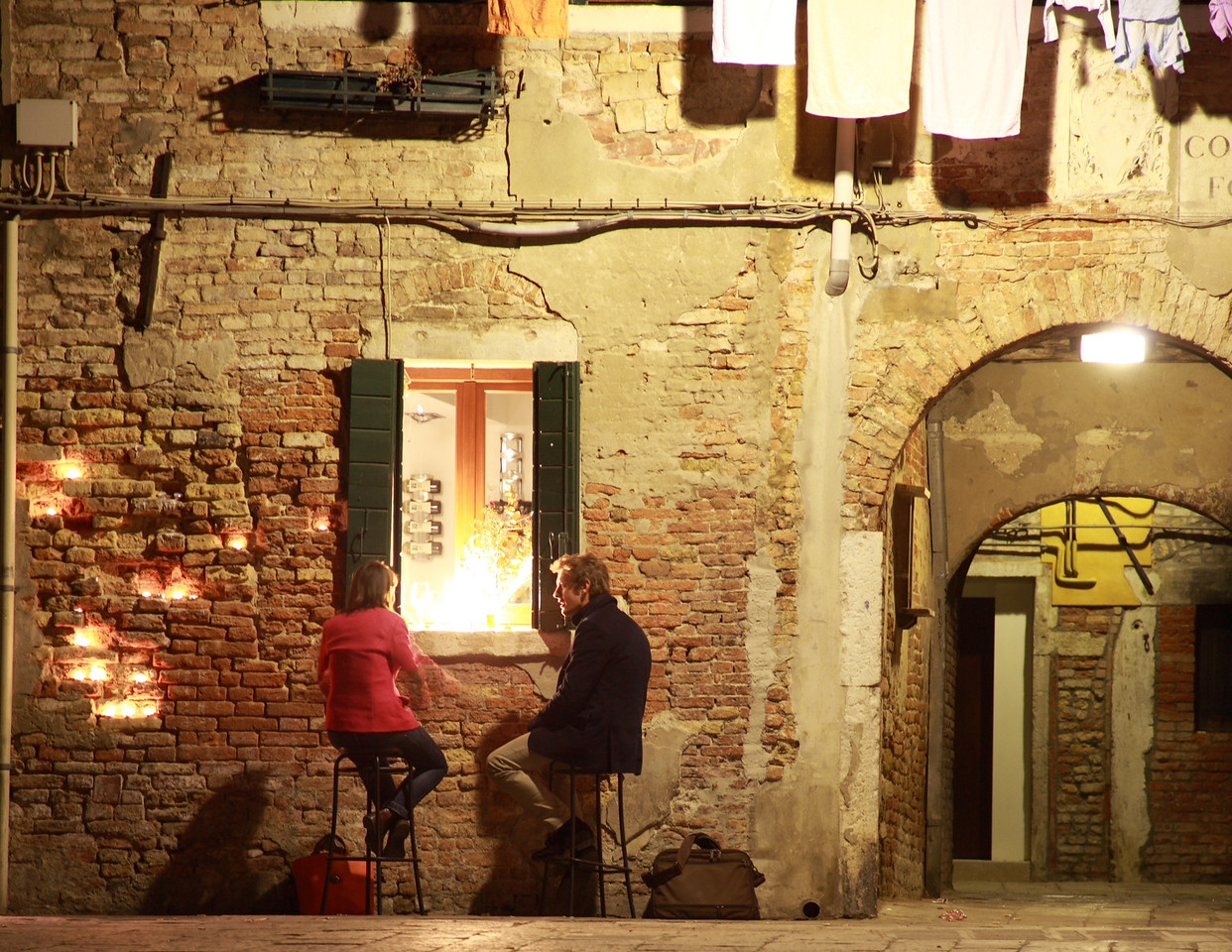 A couple chat outside a bar on a Venice piazza