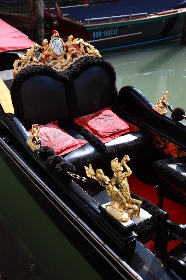 The gold, black and red seats of a gondola, Venice, Italy