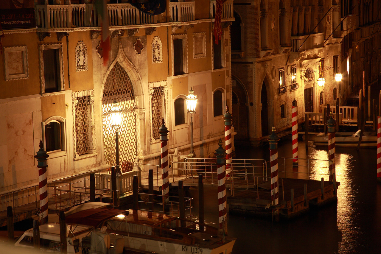 The red and white striped mooring polse of the gondolas in Venice at night