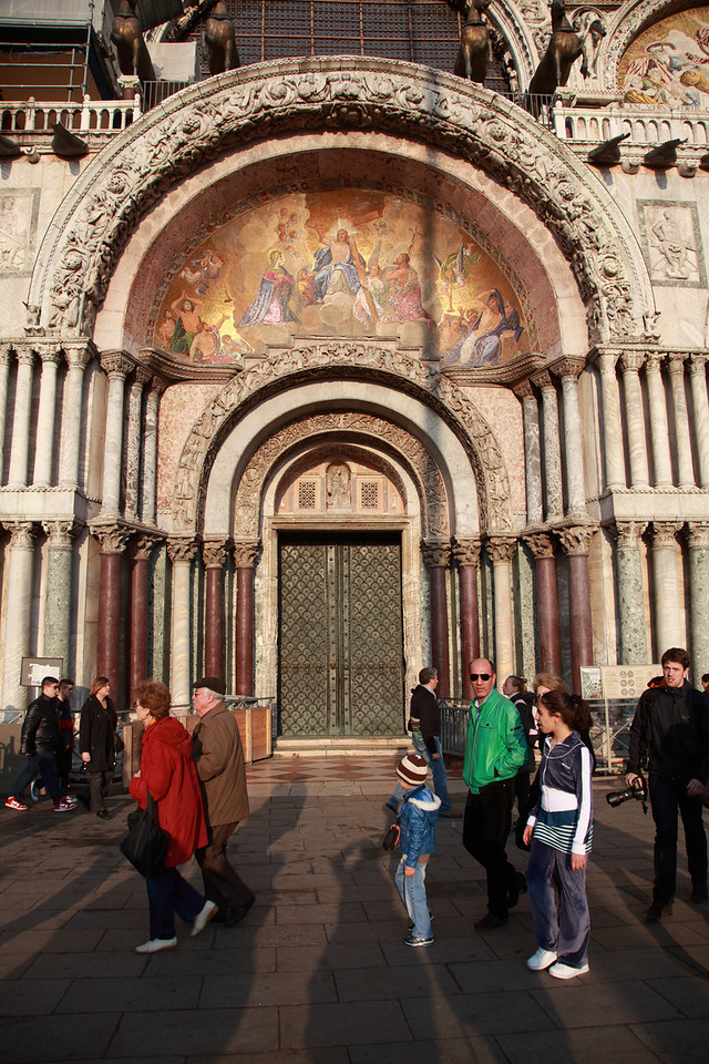 Tourists walking past the entrance to St Mark's Basilica, St Mark's Square, Venice, Italy