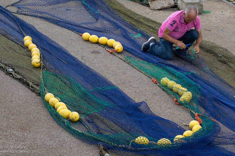 Mending fishing nets.