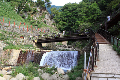 The walkway into the park. The small rock wall to the upper left of the falls and below the bridge line the shallow hot springs where the monkeys eat and bathe