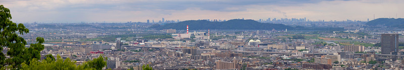 Zooming into the buildings of Osaka, from a high view point in Fushimi Inari...