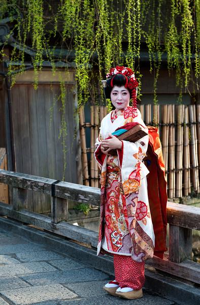 A tourist or a geisha? Most likely a tourist dressed up like a geisha to take a late afternoon stroll in Gion, Kyoto