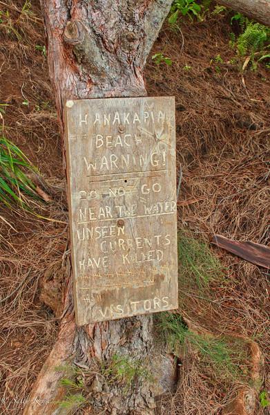 Warning sign at Hanakapi ai beach on the Kalalau Trail, Na Pali coast, Kauai, Hawaii.