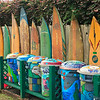 A row of surfboards and graphic garbage cans outside a B&B in Hanelei, Kauai, Hawaii