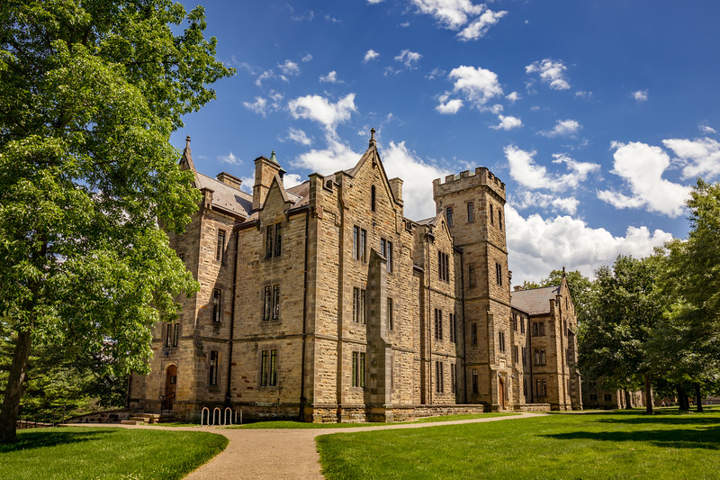 """Ascension Hall, one of the stately stone """"castles"""" that overlook the historic south campus. This masterpiece of Victorian Gothic architecture, which dates from 1859, is the home for five academic departments: classics, economics, modern languages and literatures, philosophy, and religious studies. Photographed on campus of Kenyon College in Gambier, Ohio on June 19, 2017 by Joe Frazee."""