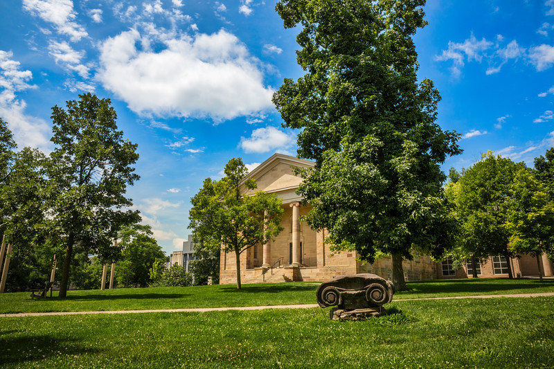 A Greek Revival beauty, Rosse Hall is a first-class, 600-seat concert and lecture hall. Projected by Kenyon's founder as one of the College's earliest buildings, Rosse Hall began life in the 1830s and since then has served a multitude of purposes, from College chapel to classroom to gymnasium. In 1999, Rosse received the addition of elegant Storer Hall, which houses the music department. Rosse Hall's front steps are home to two linked traditions cherished by Kenyon students: the Freshman Sing, in which first-year students gather after Opening Convocation to sing College songs for the first time (well, they try!); and the Senior Sing, following Commencement ceremonies, when the same students, now freshly minted graduates, return to reprise them. Photographed on campus of Kenyon College in Gambier, Ohio on July 16, 2017 by Joe Frazee.
