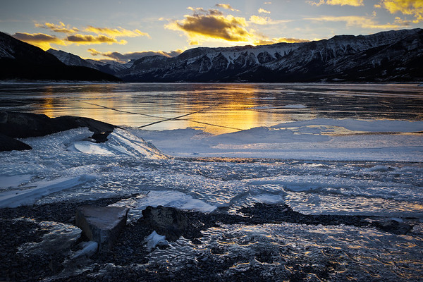 Sunset from Windy Point, Abraham Lake, looking over the ice on the shore and on the lake.