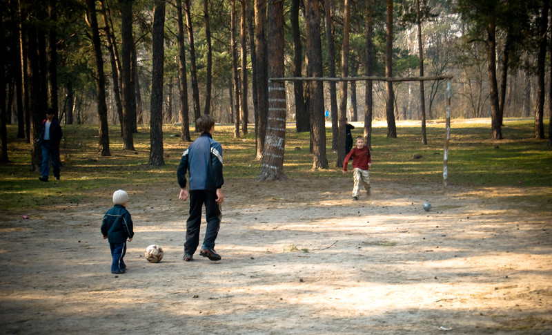 Kids playing soccer in forest