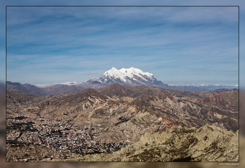 The city of La Paz, Bolivia as seen from El Alto overlooking the city with Mount Illimani in the background.  Approximate altitude at this location is 13,300 feet.  Mount Illimani is 25 miles southeast of the city of La Paz and climbs to 21,194 feet.