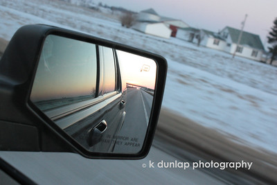 "02.06.09 = Today my sister called to inform me that I had won an all expense paid trip to Athens, Ohio!  WOW. My niece is a freshman there and we took my nephew up for little sib's weekend.  As I was sitting in the car I could see the sun setting in the side view mirror.  I was surprised to see that I also got a great farm in the frame as well.  It really made for an interesting shot.  My nephew's comic line was, ""You know your in the country when the gas station sells deer corn."""